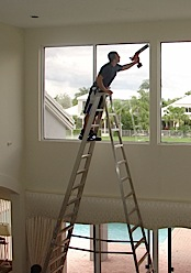 Caulking Residential home on tall ladder